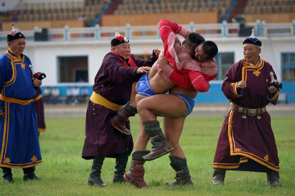Ulaanbaatar, Mongolia, July 2003. Competitors in the Mongolian Wrestling championships in the national Naadam at Ulaanbaatar central stadium. Mongolian wrestling champion Usukhbayar finally succeeds in throwing his opponent, ending a marathon 3 hour semi-final match. Usukhbayar went on to wion the final, becoming champion for the second time.